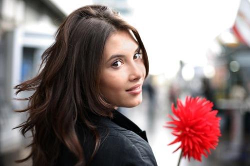 femme tenant une fleur